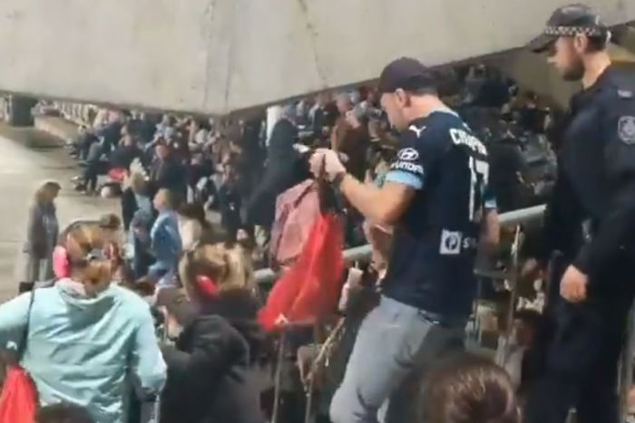 man and young girls being escorted through stadium crowd by police