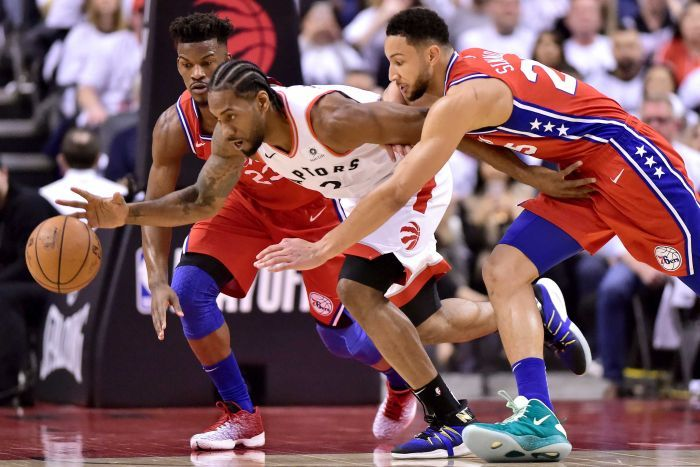 Ben Simmons, right in a red singlet, chases Kawhi Leonard, white singlet in centre, with Jimmy Butler, left, watching on