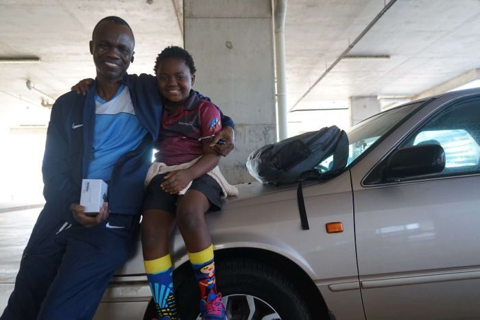 Renter Patrick Mossongo and his son sit on a car bonnet.