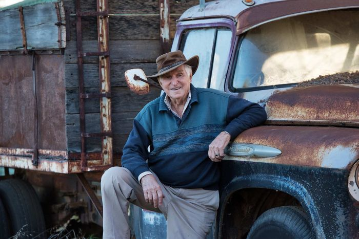 Norman Simon leaning against a Chev truck that has rusted out after years out in the weather.