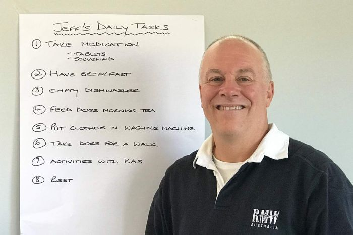 Jeff Thurlow, who has younger onset dementia, smiles as he stands beside a list on the wall to remind him of his daily tasks.