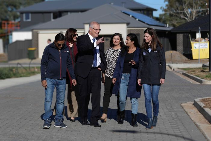 Scott and Jenny Morrison and Nicolle Flint walk with the Singh family through a residential estate under construction