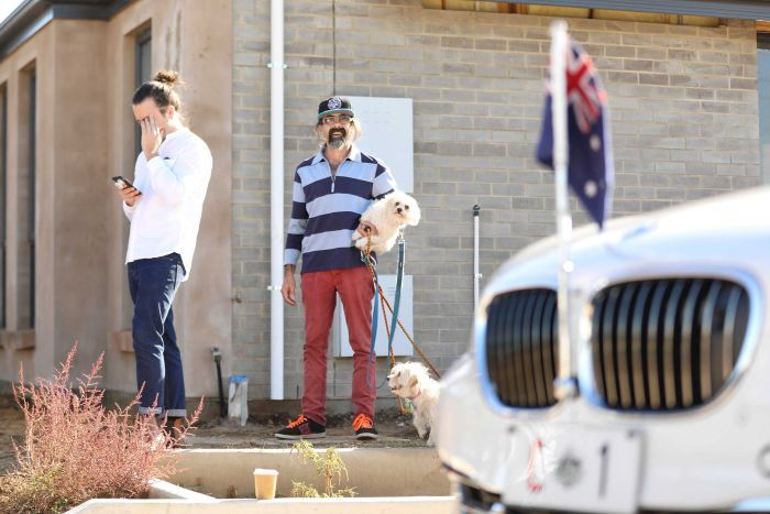 A man holds his dog as he looks towards the Prime Minister's car