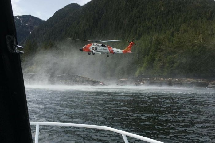 A helicopter hovers over water searching for suvivors of a seaplane crash