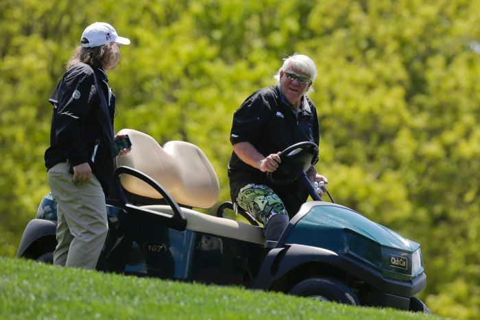 A golfer talks to a man as he gets into a golf cart on a grassy slope.