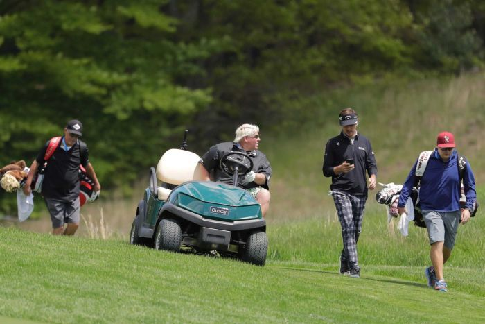 A golfer in a golf cart talks to another golfer as they go down a fairway.