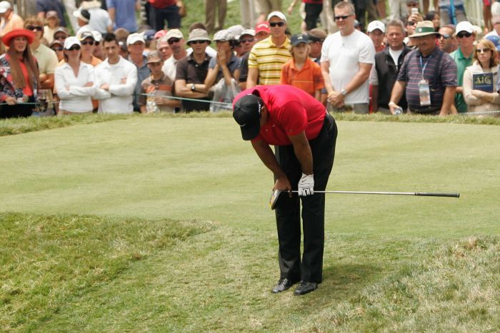 A golfer bends over on the tee in obvious discomfort holding his knee.