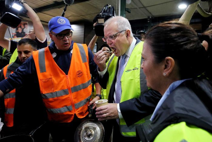 Scott Morrison eats a chestnut in the markets while Jenny Morrison watches on