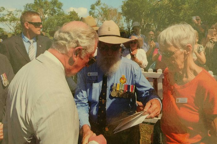 Prince Charles in Darwin in 2017 with older couple looking at poetry book.