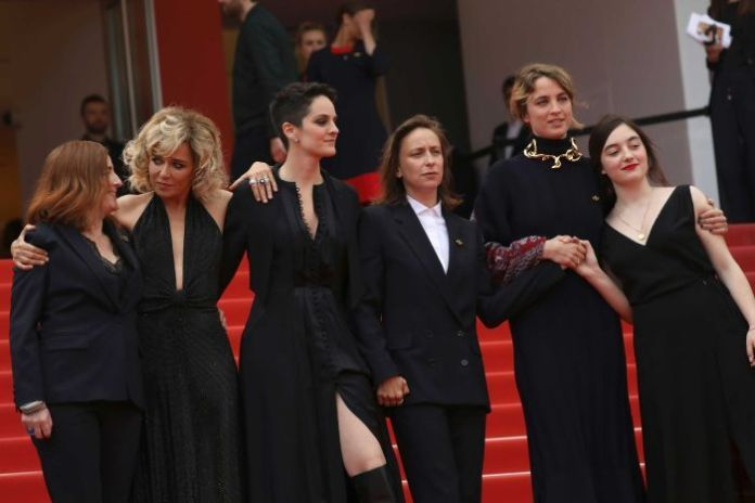 A group of women in formal wear poses for photographers on the red carpet in Cannes.