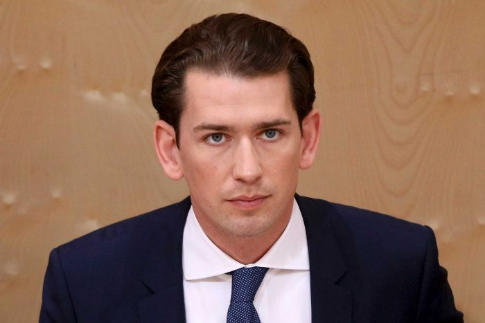 A close up of Sebastian Kurz wearing a dark blue suit and tie with brown hair and blue eyes.
