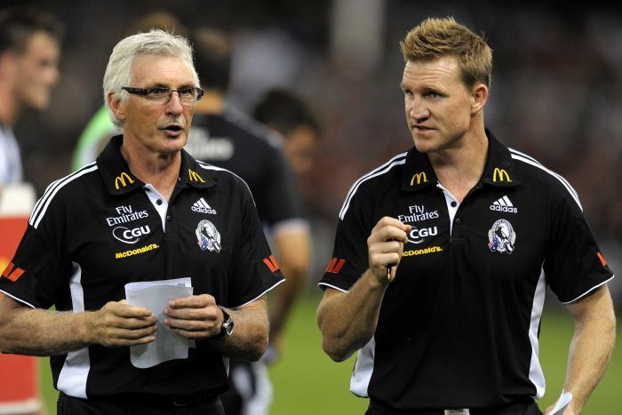 Two members of the Collingwood coaching staff in discussion on the ground at Docklands.