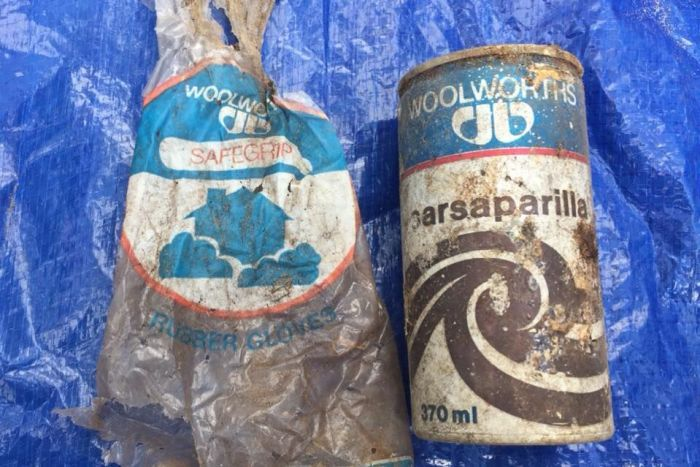 A dirty branded plastic bag and drinking can lie on a blue tarp.