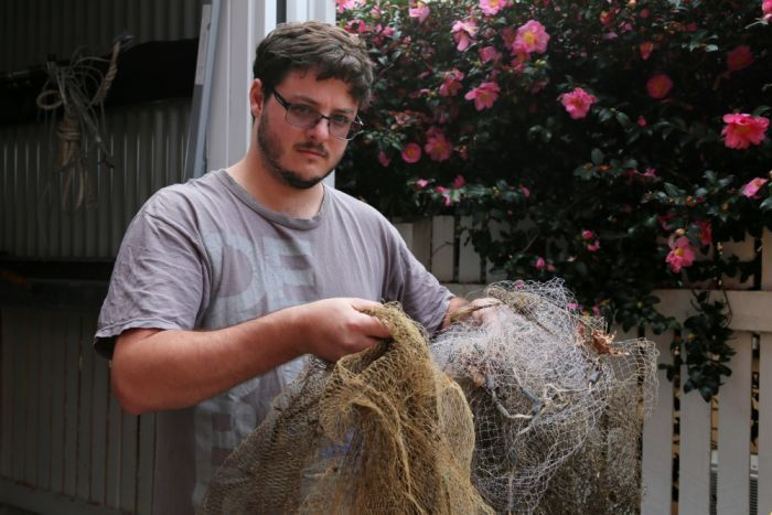 A man holds old casting nets in front of a shed.
