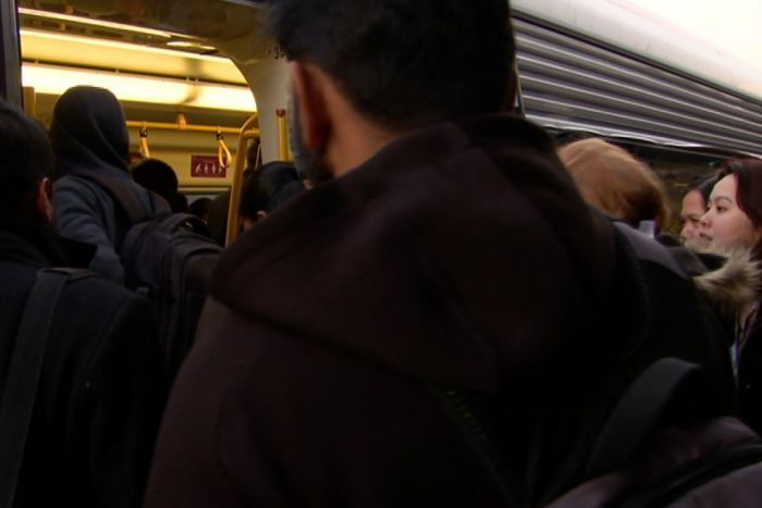 Commuters crowd through the doors of a train in Wyndham, Melbourne.
