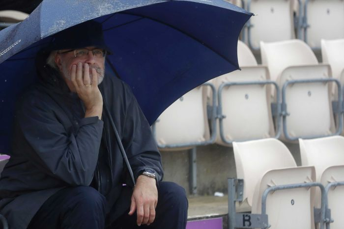 A man sits under an umbrella cupping his chin in one hand