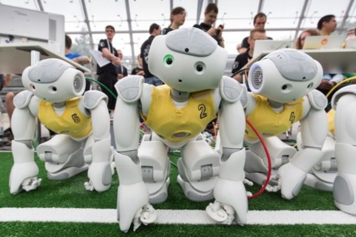 A robot soccer team wearing yellow vests waits on the side lines.