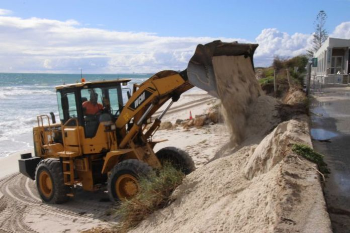 An excavator rides the sand at Port Beach after a storm erosion.