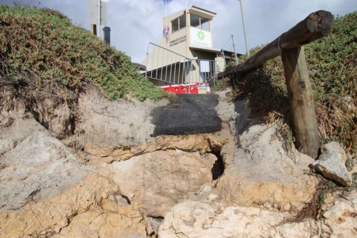A close-up of a collapsed path leading from Fremantle & # 39; s Port Beach to a surf life club.