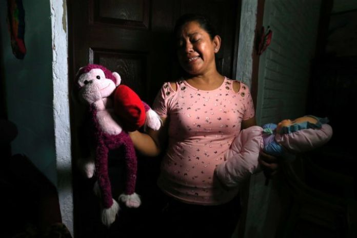 Rosa Ramirez sobbs as she shows the toys that belonged to her granddaughter.