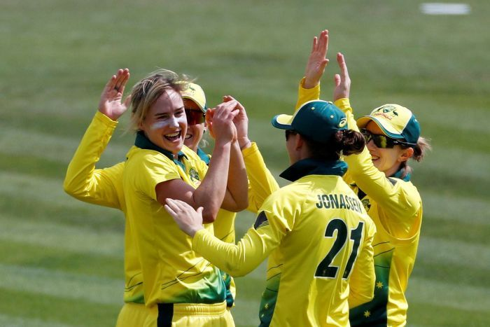 Ellyse Perry smiles and slaps hands with three teammates