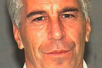 A photo of Jeffrey Epstein smiling at the camera against a blank background.