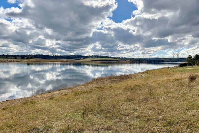 Pejar Dam with water, green grass, windmills and clouds in the sky