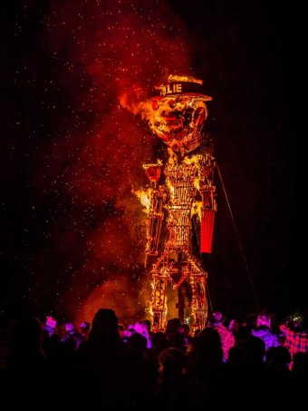 A large wicker man is set alight at night in front of a crowd of onlookers.