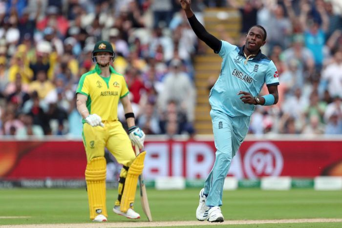 Joffra Archer raises his arm and wheels away as Steve Smith looks on dejectedly