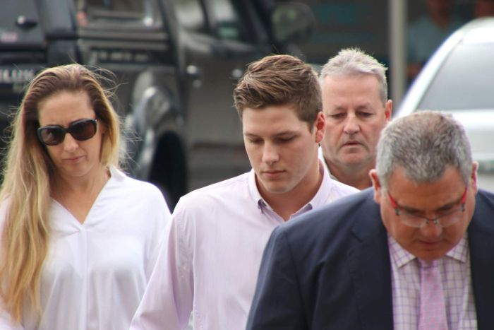 Timothy England walks with his parents and lawyer outside court in Cairns.