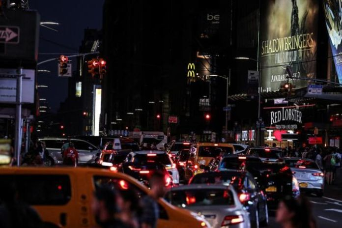 Yellow cars and taxis are located near Times Square, with most of the screens wrapped in darkness.