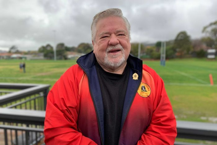 An elderly man dressed in a rugby training suit stands at the field