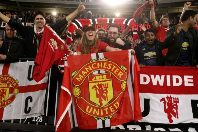 Encouraging fans waving Manchester United flags.