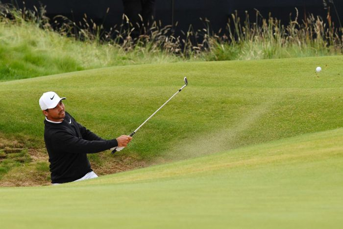 Sand flies behind the ball as Jason Day - partially obscured while standing in a bunker - completes a casual shot.