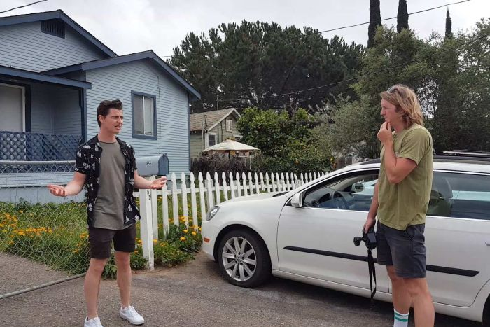 Two men arguing out the front of a blue house.
