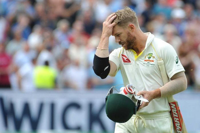 Australia batsman David Warner brushes his hair back as he walks off the ground with his head down.