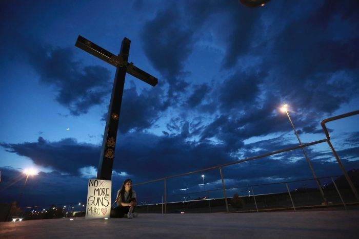 A cross against a dark blue sky with a woman sitting at its base with a sign saying No more guns, make love.
