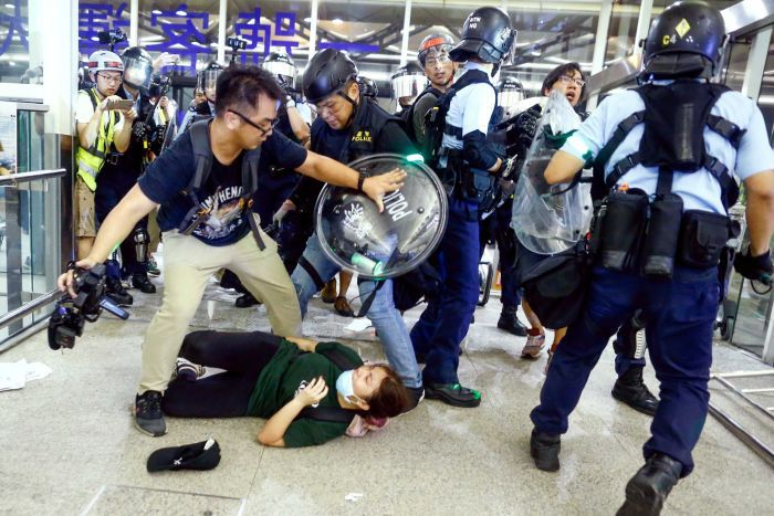 A man pushes back riot police at Hong Kong airport as a woman lays on the ground.