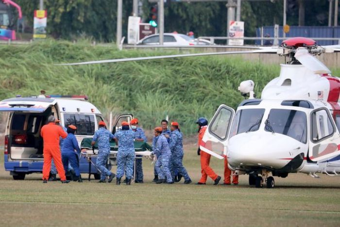 Officials in blue camouflage print transport a body on a stretcher from a helicopter to a van.