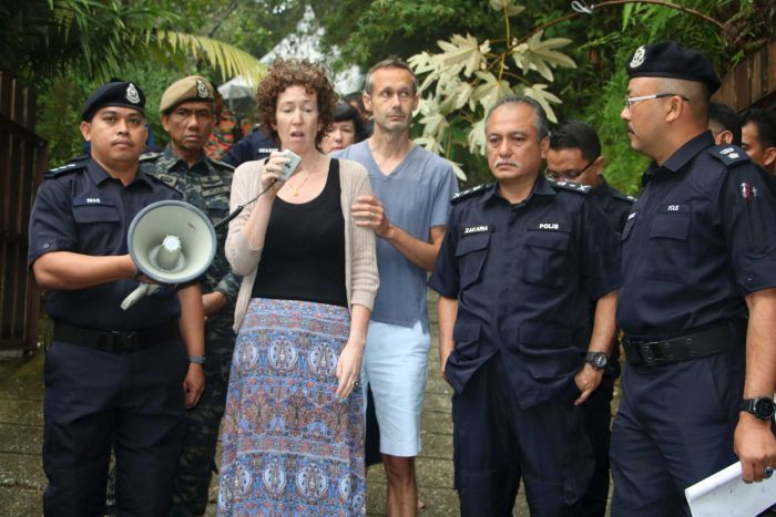Meabh Quoirin holds a microphone in her hand as police surround her. Her husband stands behind her in the forest.