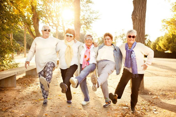 Five women wearing novelty sunglasses link arms and each kick a leg out as if dancing, while smiling or laughing.
