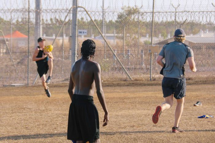 A young indigenous man, with his back to camera, watches on as another young man in a cap takes a mark in a game of football.