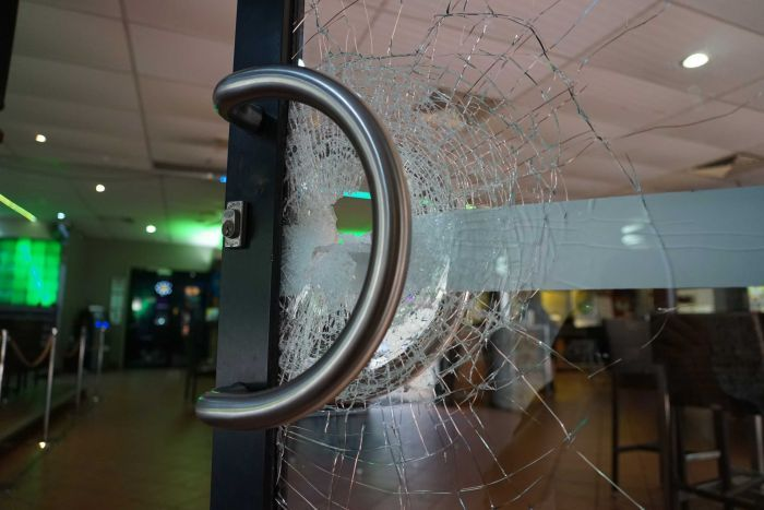A glass door is seen with cracks running through it, with a hole in the middle. The green light of the bar is visible behind it.