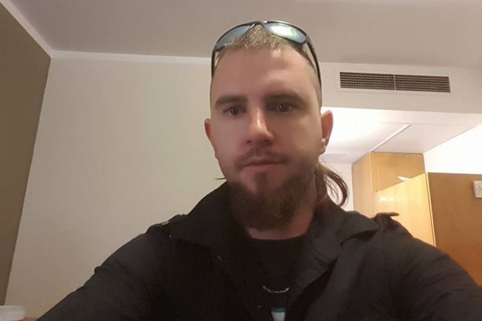 A selfie of a man with a mullet wearing a black jacket.