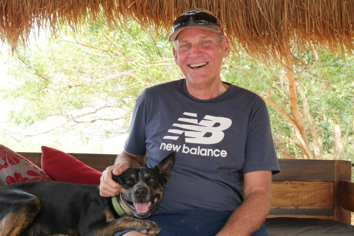 Man smiling at camera with dog resting on lap.