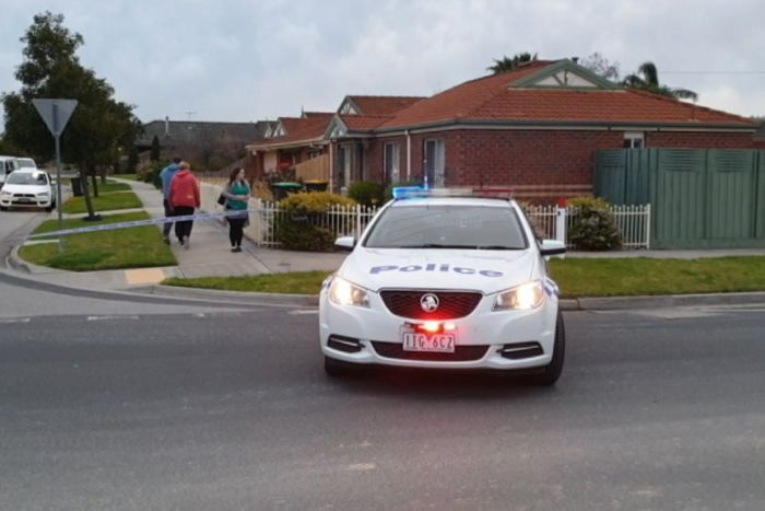 A police car sits on a road in front of a brick house.