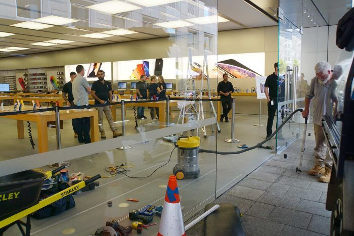 A wide shot showing people inside the Apple Perth City store as a  man with a vacuum cleaner cleans up at the entrance.