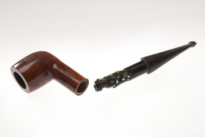 Against a grey backdrop, you see a radio receiver concealed in a smoking pipe.