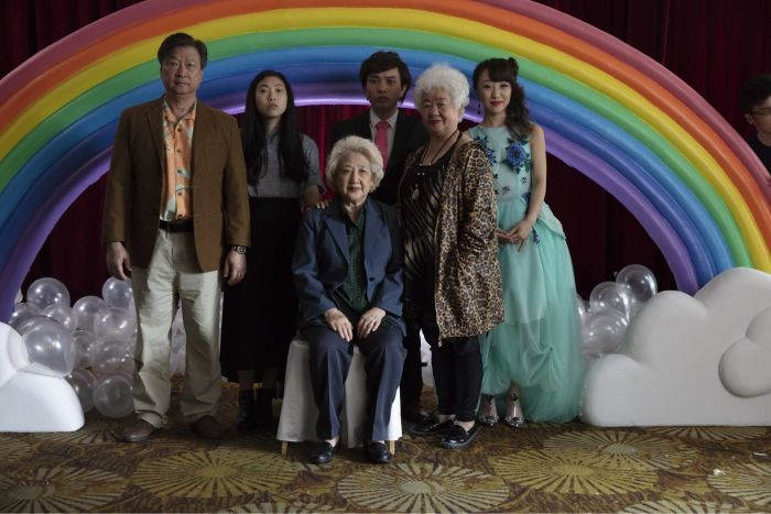 A Chinese family poses for a portrait in front of a rainbow