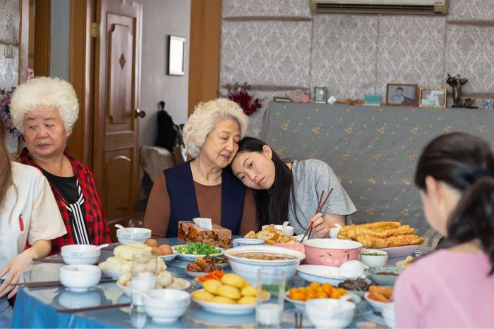 A young Chinese woman rests her head on her grandmother, they sit at a table filled with food